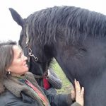 Fiona-Robertson-Body-&-horse-Whisperer-fiona-next-to-a-beautiful-large-black-horse.