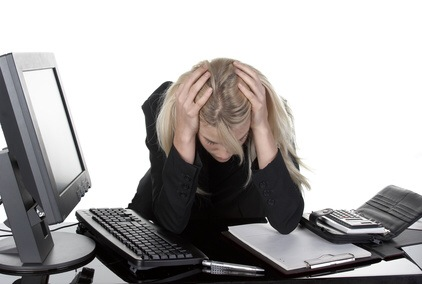 Womens-anger-affecting-her-body-fatigue-depressed-woman-at-her-desk-head-in-hands