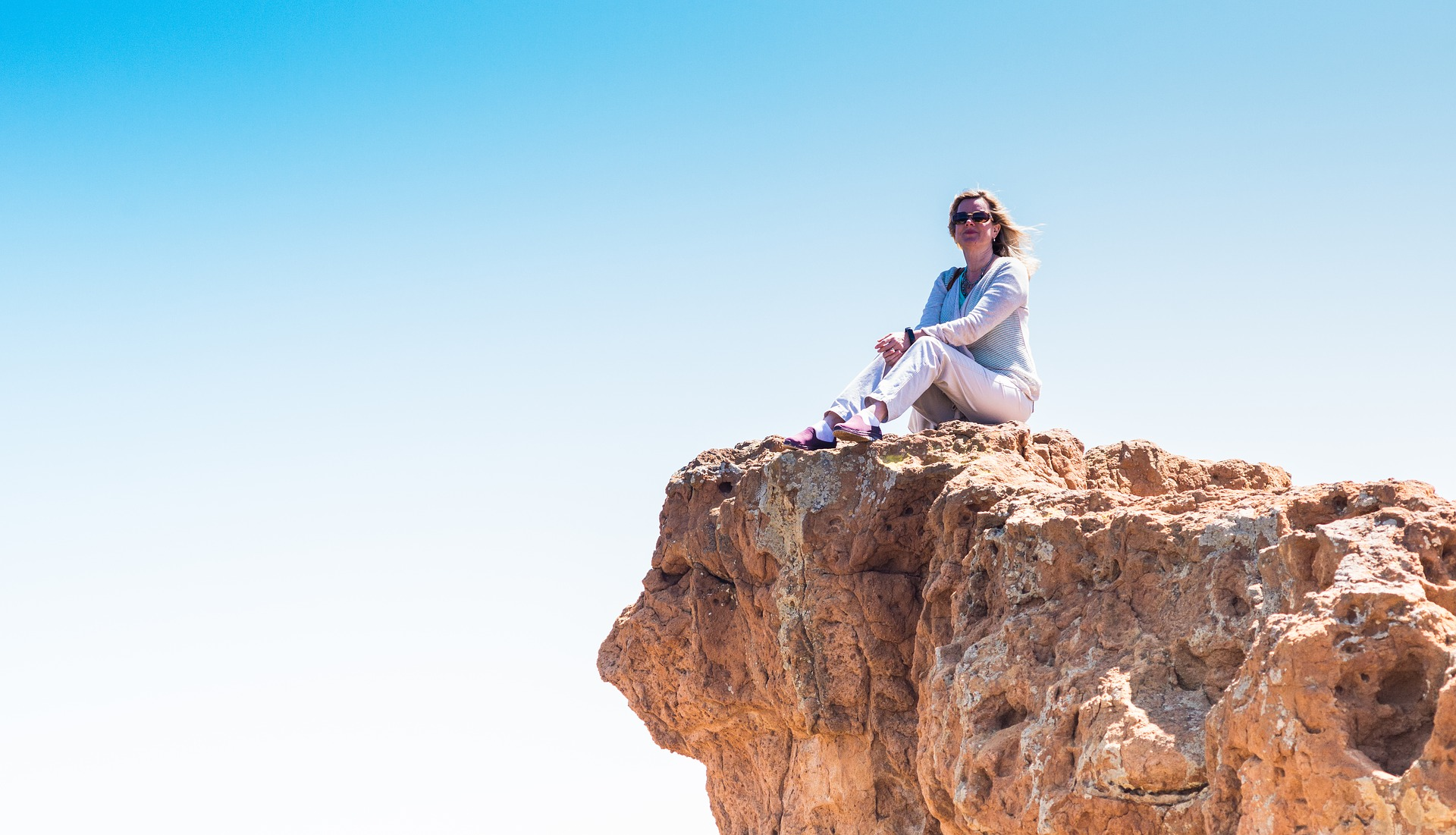 Woman-feeling-free-sitting-on-top-of-the-world